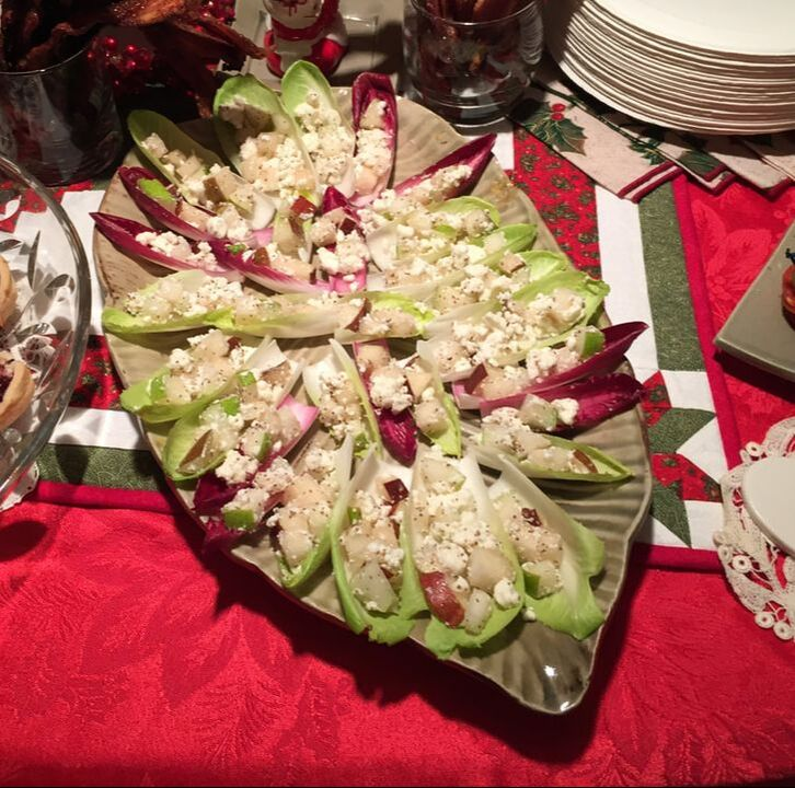 Red tablecloth and Christmas linens with a green, leaf-shaped platter holding many green and red Belgian endive leaves filled with diced pear and feta cheese.