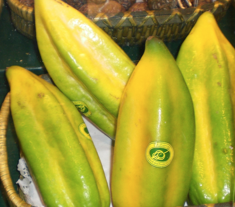 Four ripe 5-sided babaco fruits showing green to yellow skin. Three fruits exhibit oval produce stickers.